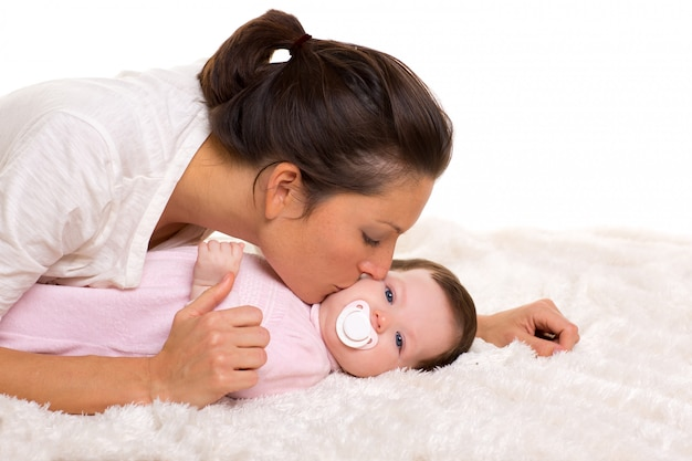 Bébé fille et mère allongée heureuse jouant ensemble Photo Premium