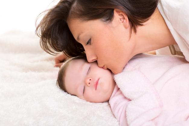 Bébé fille et mère l'embrassant couché heureux sur blanc Photo Premium