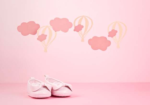 Bébé Fille Mignonne Chaussures Roses Sur Le Fond Pastel Rose Avec Des Nuages ?? Et Des Ballons Photo Premium