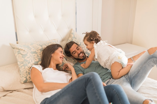 Bébé fille passe du temps avec ses parents au lit Photo gratuit