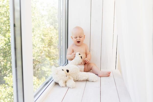 Bébé Garçon De 8 Mois Couché Dans Des Couches Sur Un Lit Blanc Avec Une Bouteille De Lait à La Maison Les Jambes Vers Le Haut, Vue De Dessus, Concept D'aliments Pour Bébé, Eau Potable Pour Bébé à Partir D'une Bouteille Photo Premium