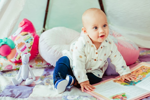 Bébé Garçon Qui Touche Le Livre En Détournant Les Yeux Photo gratuit