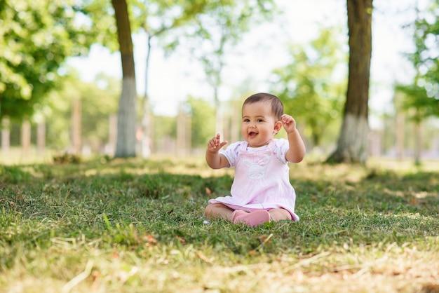 Bébé Heureux Dans Une Robe Rose Est Assis Sur L'herbe Dans Le Parc. Petite Fille Plaing Sur L'herbe Verte. Photo Premium