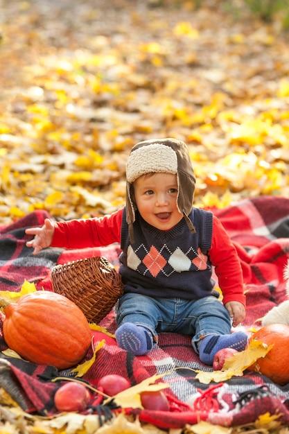 Bébé heureux avec pull assis sur une couverture Photo gratuit