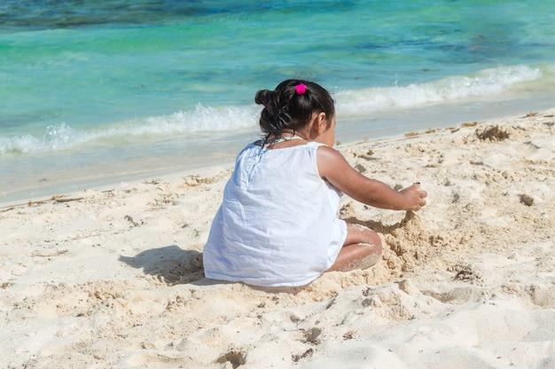 Bébé Jouant Dans Le Sable Près De La Mer. Petite Fille Assise Sur La Plage. Silhouette De Petite Fille Avec La Mer. Construire Un Château De Sable Photo Premium