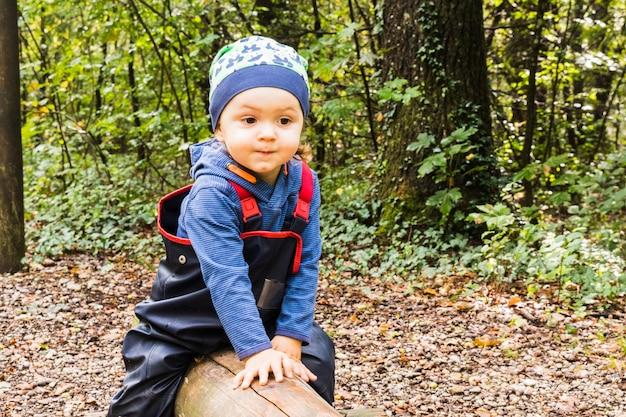 Bébé jouant sur un sentier forestier en automne Photo Premium