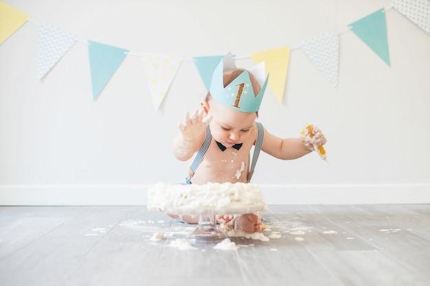 Bébé joue avec un gâteau lors de son anniversaire d'anniversaire Photo Premium