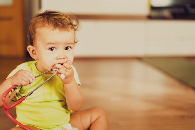 Bébé Joue Avec Un Stéthoscope Médical Sur Le Sol De Sa Maison, Concept De Pédiatrie. Photo Premium