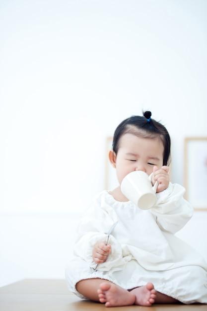 Bébé mange des aliments pour bébé sur la table blanche. Photo Premium