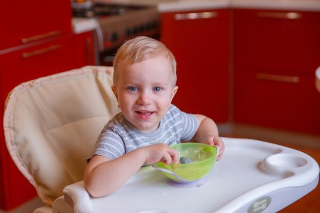 Bébé mange des flocons d'avoine. petit déjeuner bébé Photo Premium