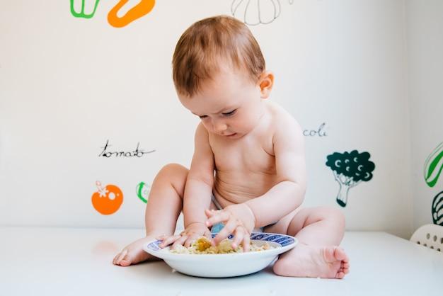 Bébé mange seul apprenant par la méthode de sevrage dirigée par bébé Photo Premium