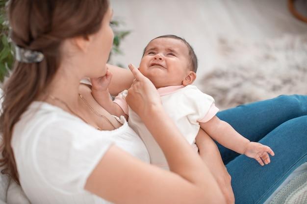 Le Bébé Pleure Dans Les Bras De Sa Mère. Une Femme Essaie De Calmer Son Petit Enfant. Photo Premium