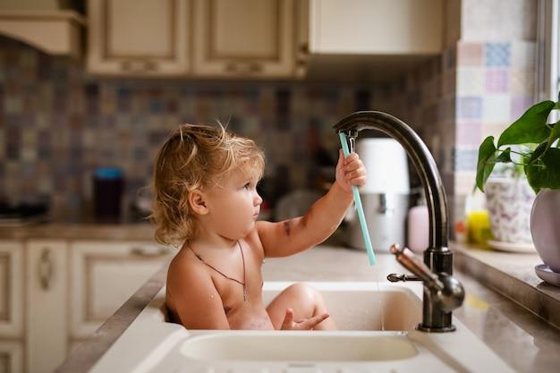 Bébé prenant son bain dans un évier de cuisine. enfant jouant avec de l'eau dans une cuisine ensoleillée avec fenêtre. Photo Premium