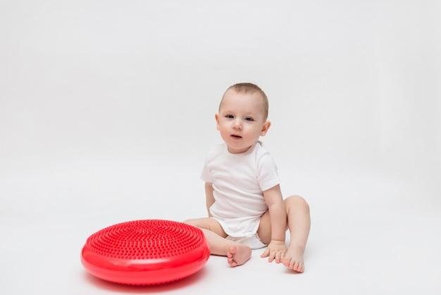Le Bébé S'assoit Et Joue Avec Le Coussin D'équilibrage. équilibreur Rouge. Orthopédiste Photo Premium