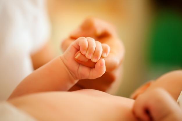 Bébé tenant la main de la mère Photo Premium