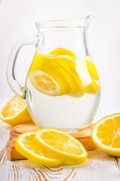 Un bécher en verre et un pichet de limonade froide sur un fond en bois blanc entouré de citrons. Photo Premium