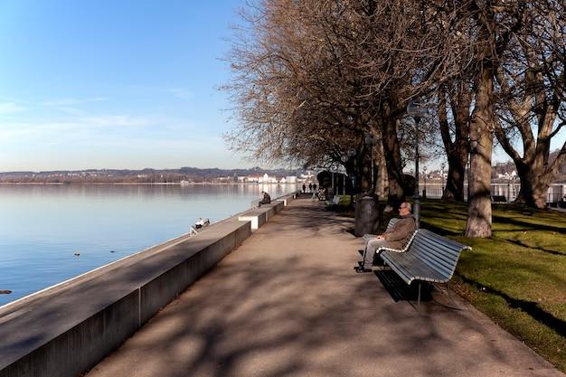Begenz / Autriche - Janvier 2020: Les Gens Se Détendent Sur Des Bancs Et Marchent Le Long De La Promenade Du Lac De Constance (bodensee) à Bregenz. Photo Premium