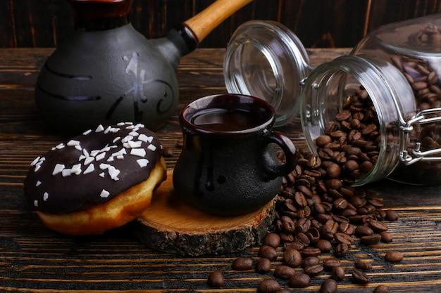 Beignet Avec Glaçage Noir Et Chocolat En Poudre Et Une Authentique Tasse De Café Fort. Une Boîte De Grains De Café Et De Céréales Coulées. Photo Premium