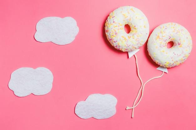 Beignet sur rose, minimalisme alimentaire créatif, beignet en forme de ballon dans le ciel avec nuages, vue de dessus avec espace de copie, tonifié Photo Premium