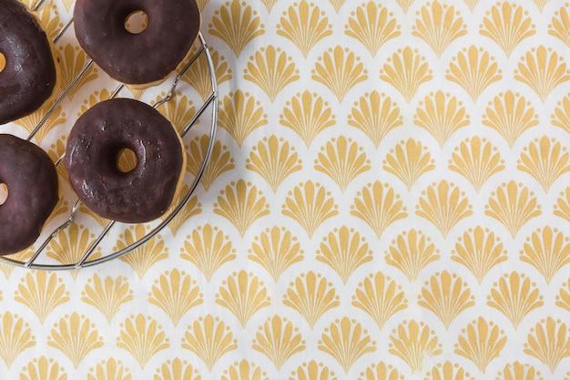 Beignets de chocolat sur une grille en métal sur le papier peint doré Photo gratuit
