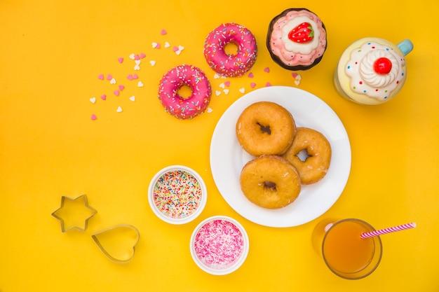 Beignets, jus, petits gâteaux et coupe-pâte sur fond jaune Photo gratuit