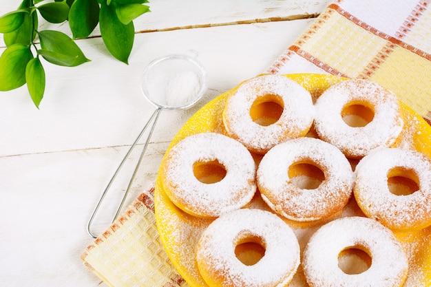 Beignets en poudre de sucre en poudre sur une serviette à carreaux Photo Premium