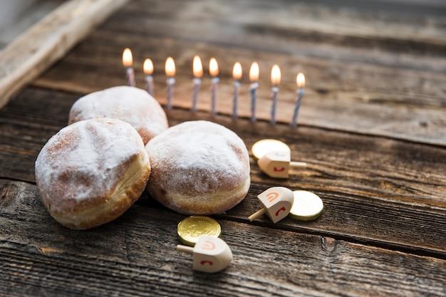 Beignets et symboles de hanoukka près de bougies Photo gratuit