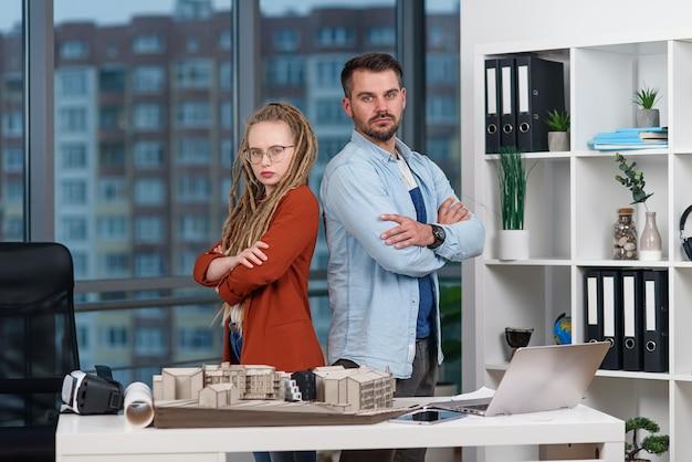 Bel Architecte Professionnel Se Tient Dos à Dos Avec Une Jolie Collègue Avec Des Dreadlocks à Photo Premium