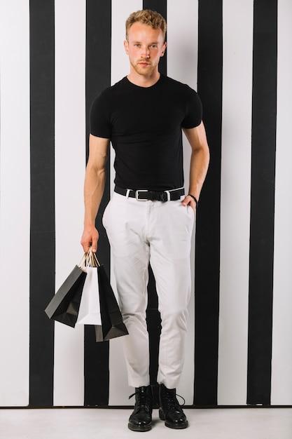 Bel Homme Adulte Portant Des Sacs De Shopping Photo gratuit