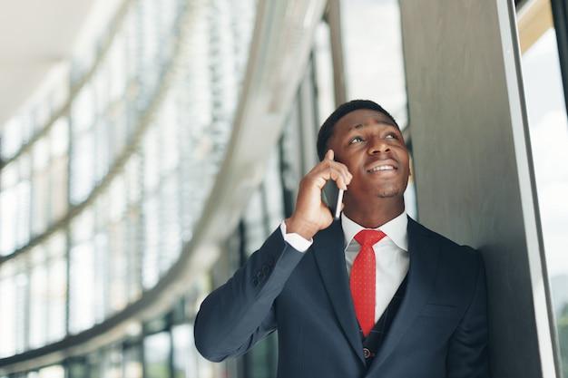 Bel homme d'affaires afro-américain, parler au téléphone portable au bureau moderne Photo Premium
