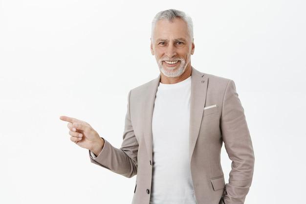 Bel Homme D'affaires âgé Prospère Pointant Le Doigt Gauche Photo gratuit