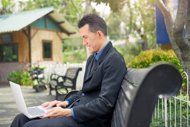 Bel homme d'affaires asiatique travaillant avec un ordinateur portable Photo Premium