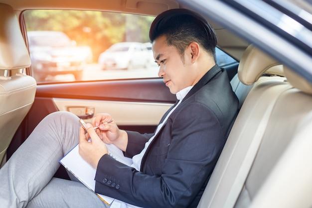 Bel homme d'affaires assis sur la banquette arrière de la voiture et de toucher le téléphone Photo Premium