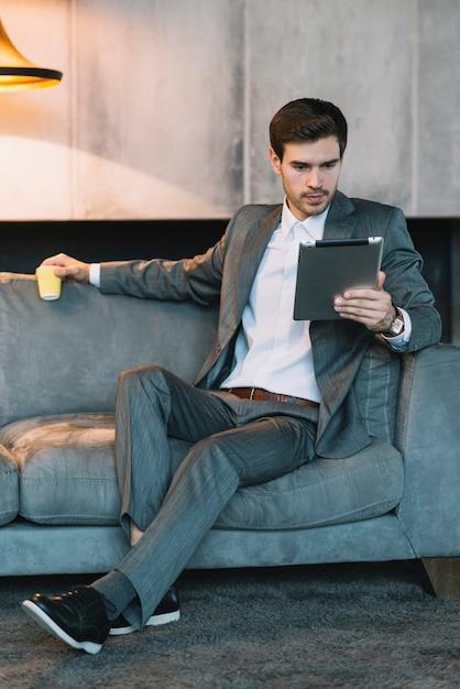 Bel homme d'affaires, assis sur le canapé tenant une tasse jetable en regardant tablette numérique Photo gratuit