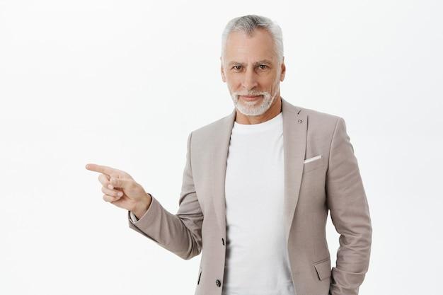 Bel Homme D'affaires Aux Cheveux Gris, Doigt Pointé Vers La Gauche Photo gratuit