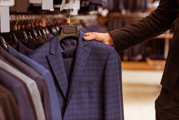 Bel homme d'affaires choisissant costume classique. Photo Premium