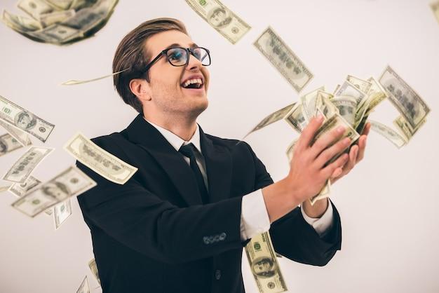 Bel homme d'affaires en costume et lunettes attrape de l'argent. Photo Premium