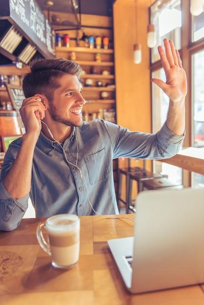 Bel homme d'affaires dans les écouteurs utilise un ordinateur portable. Photo Premium