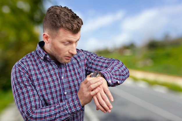 Bel homme d'affaires jeune étonné pointant sur la montre Photo Premium