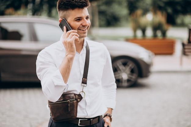 Bel Homme D'affaires Parlant Au Téléphone Près De Sa Voiture Photo gratuit