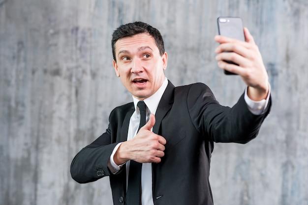 Bel homme d'affaires avec le pouce en prenant selfie Photo gratuit