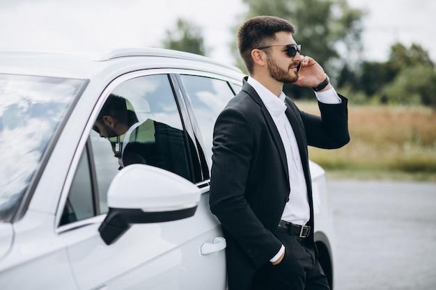 Bel homme d'affaires près de la voiture blanche Photo gratuit