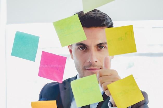 Bel homme d'affaires à la recherche de notes autocollantes droites et le pouce dans des verres se trouve dans creat Photo Premium