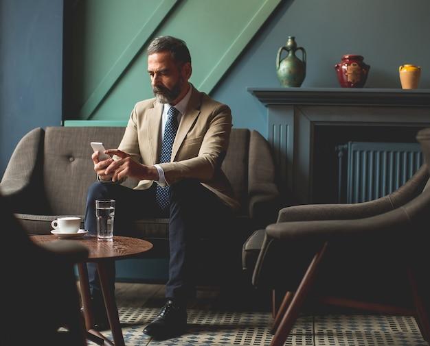 Bel homme d'affaires senior, boire du café et utiliser un téléphone portable dans le hall Photo Premium