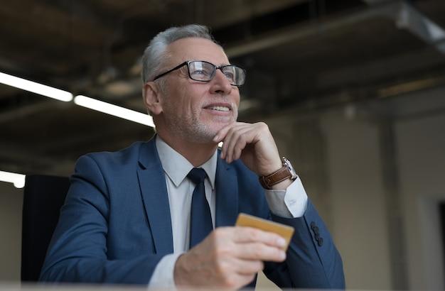 Bel Homme D'affaires Senior Tenant Une Carte De Crédit Or Photo Premium