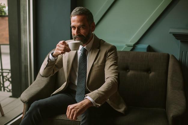 Bel homme d'affaires sérieux élégant assis dans un fauteuil et tenant une tasse d'espresso. Photo Premium