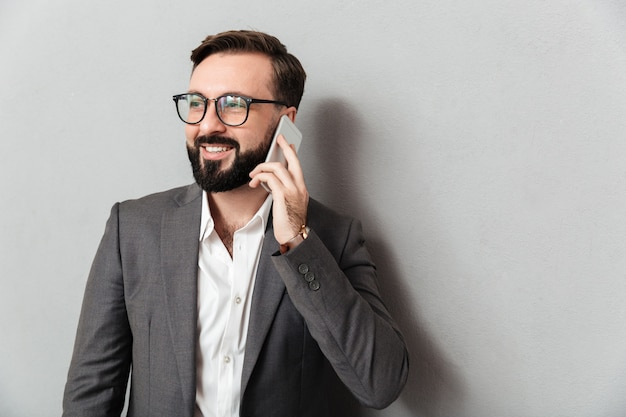 Bel Homme D'affaires En Tenue De Soirée Ayant Une Conversation Mobile à L'aide De Smartphone Isolé Sur Gris Photo gratuit