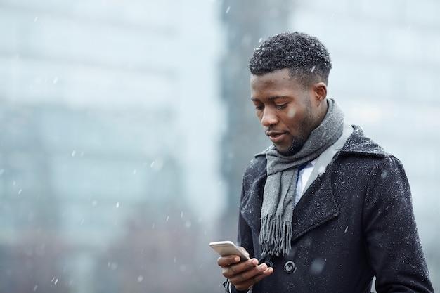 Bel homme africain avec smartphone dans la neige Photo gratuit