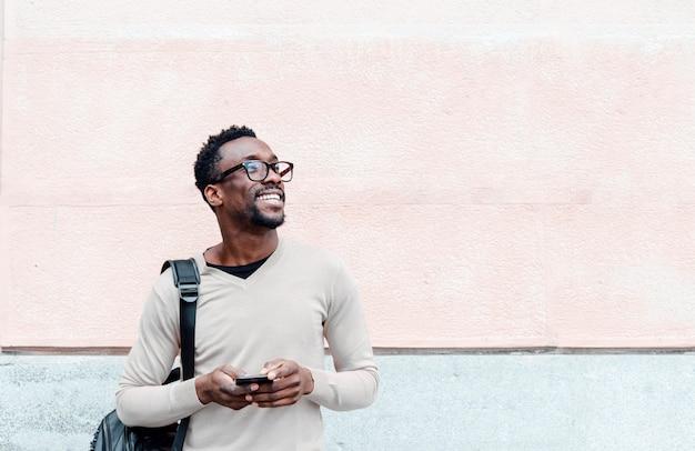 Bel Homme Afro-américain à L'aide De Smartphone Dans La Rue Photo Premium