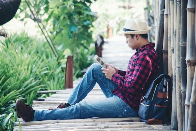 Bel homme à l'aide d'un ordinateur portable dans la nature du voyage Photo gratuit